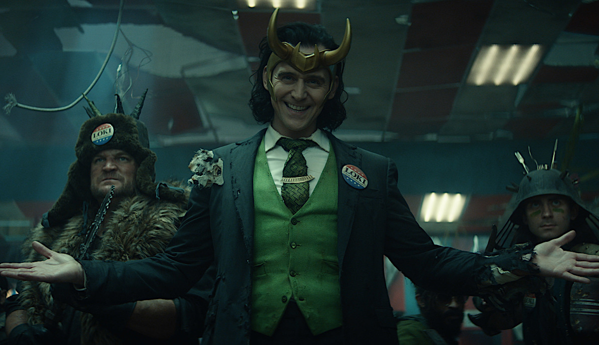 Tom Hiddleston smiles deviously in a green vest and tie, black blazer, and gold crown with a red, white, and blue pin that reads 'Loki' in Marvel's 'Loki' TV series on Disney+.
