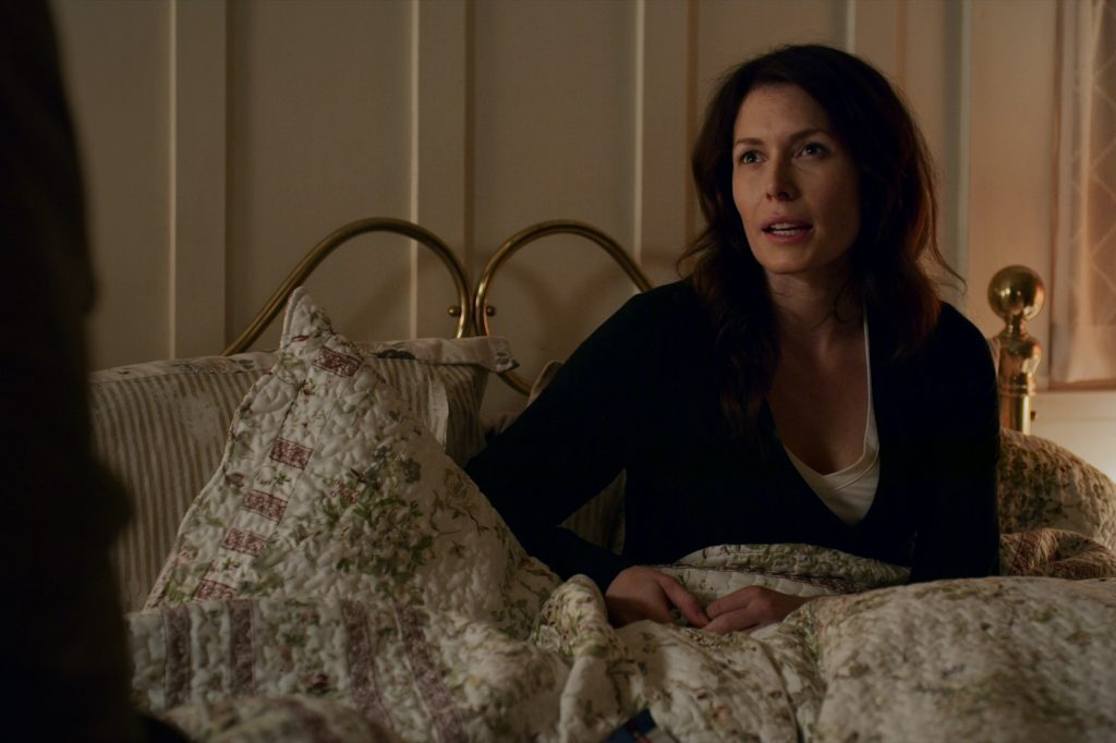 Lauren Hammersley as Charmaine Roberts sitting in a bed on 'Virgin River'