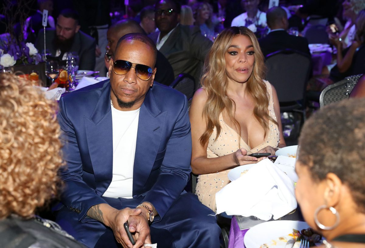 Wendy Williams looking away from the camera while wearing a gold dress and sitting next to Kevin Hunter wearing an all-blue suit.