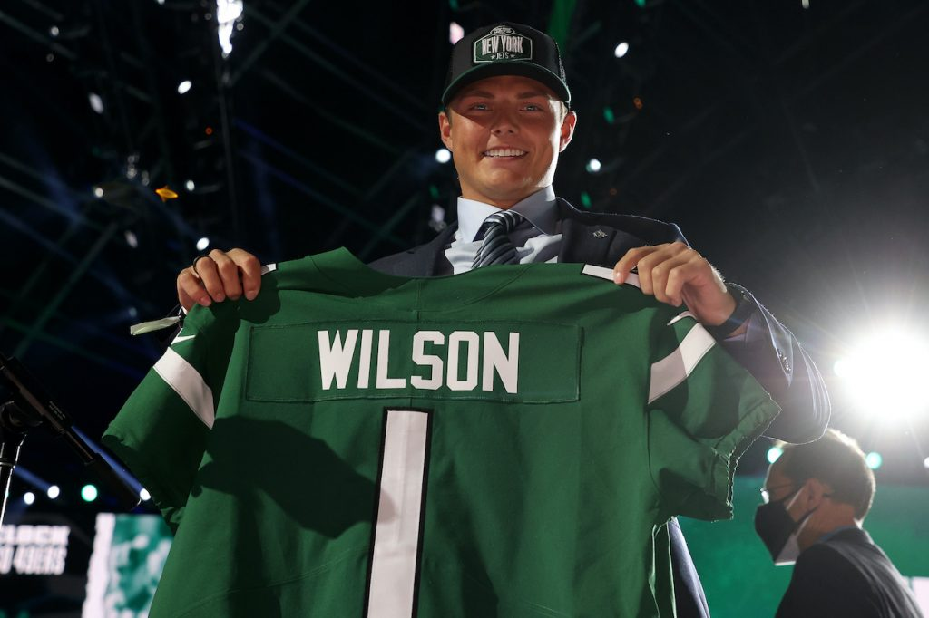 Zach Wilson holds a Jets jersey onstage after being drafted second at the 2021 NFL draft