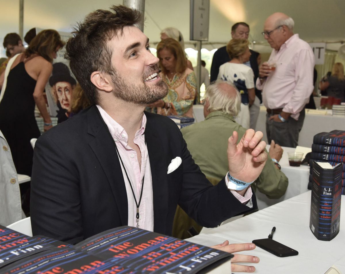 AJ Finn/Dan Mallory signs copies of the Woman in the Window at an event