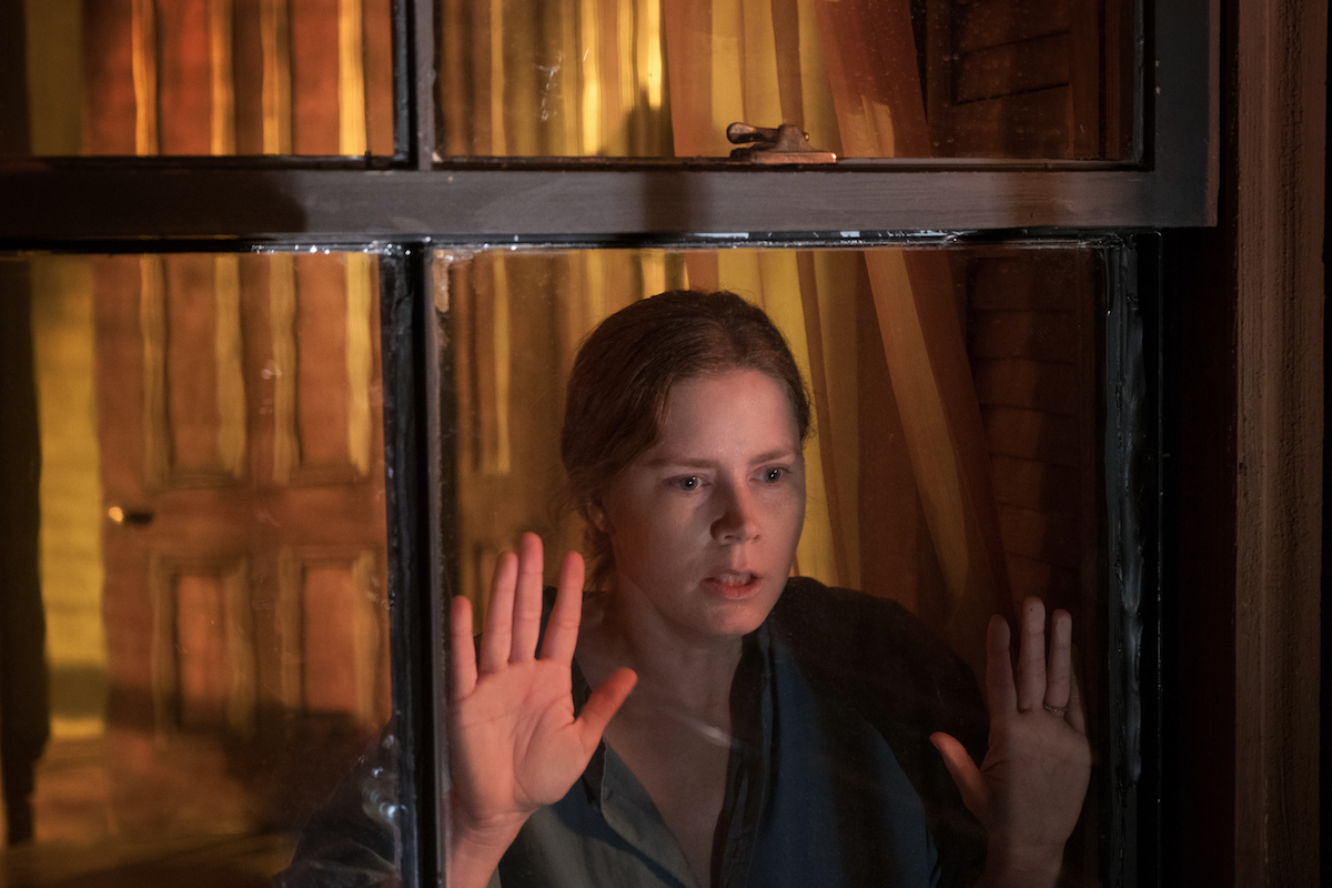 Amy Adams looking out window with hands against the glass in The Woman in the Window