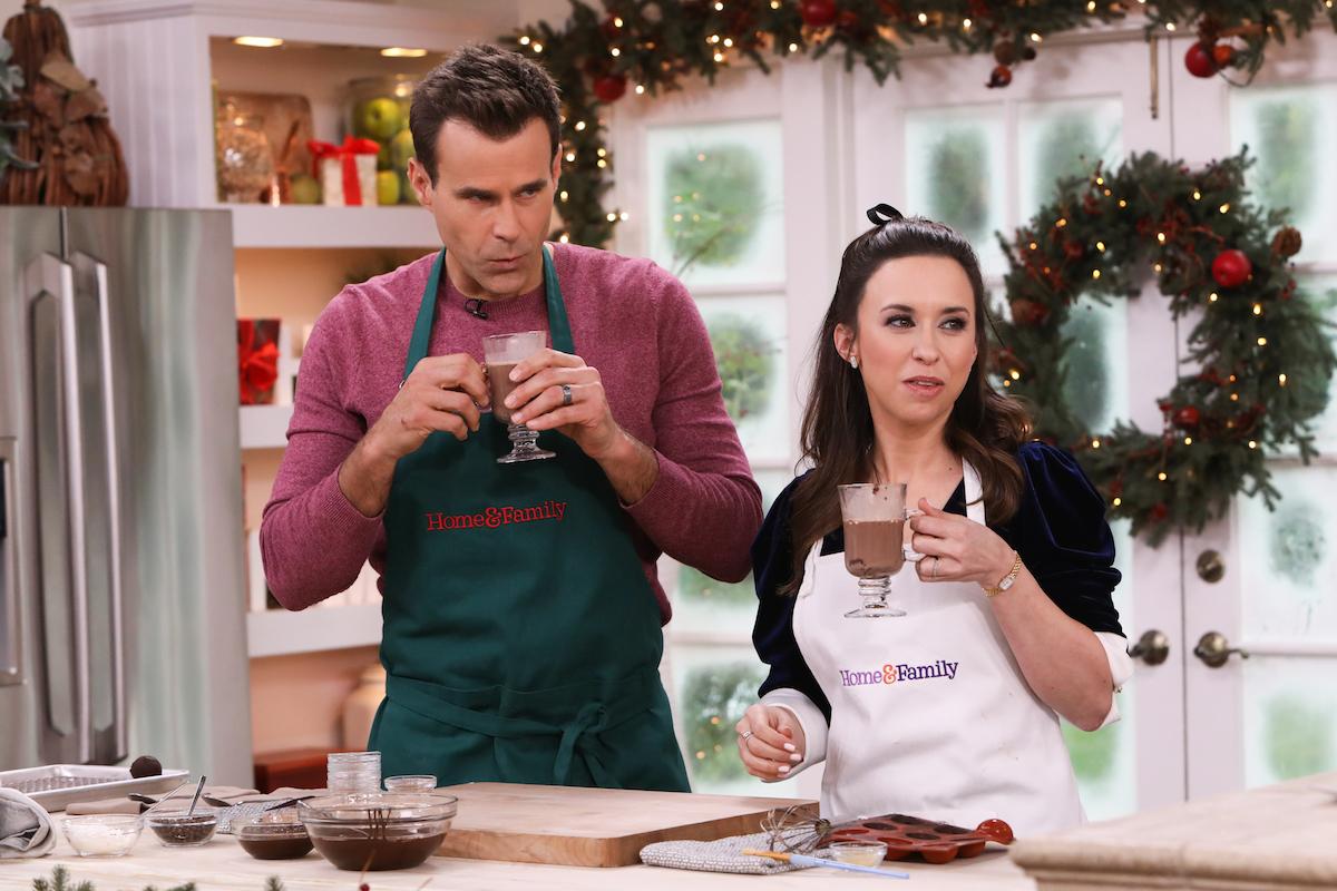 Cameron Mathison and Lacey Chabert holding mugs of hot chocolate