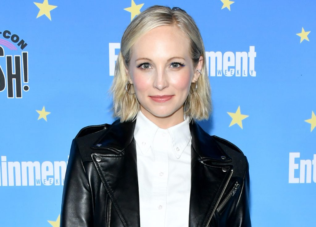 Candice King with short blonde hair in a white top, black leather jacket, black leather shorts, and rainbow-colored high heels