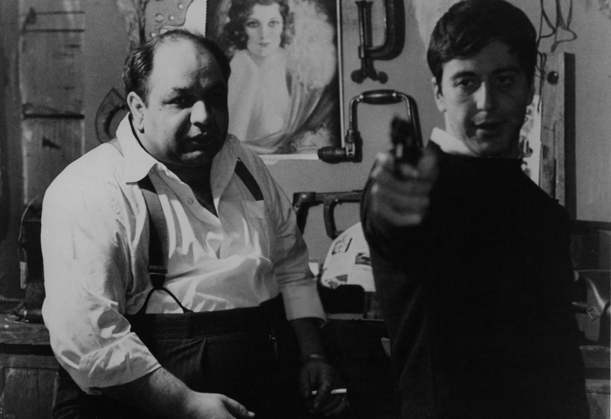 Al Pacino points a pistol as Richard Castellano looks on a scene from 'The Godfather.'