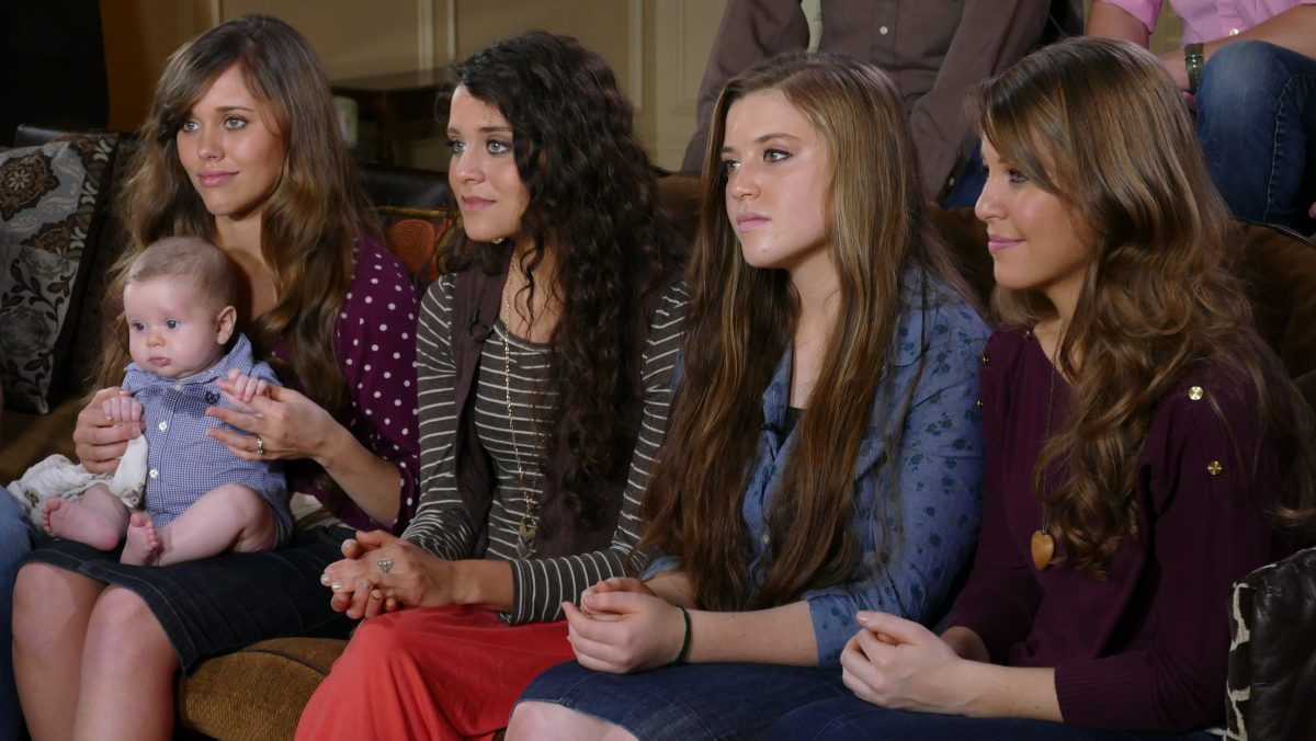 Duggar sisters sitting on a couch