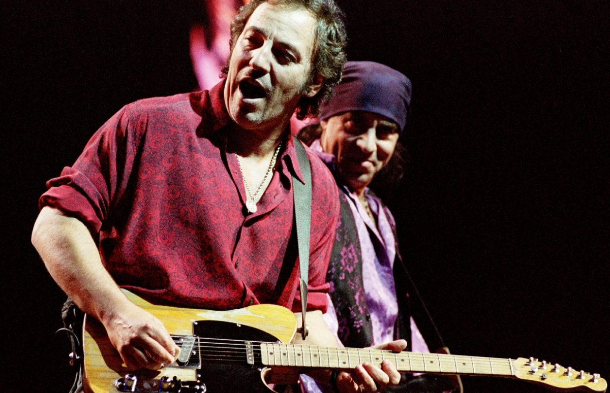 Bruce Springsteen sings and plays guitar on stage as Steven Van Zandt plays guitar and smiles at Springsteen.