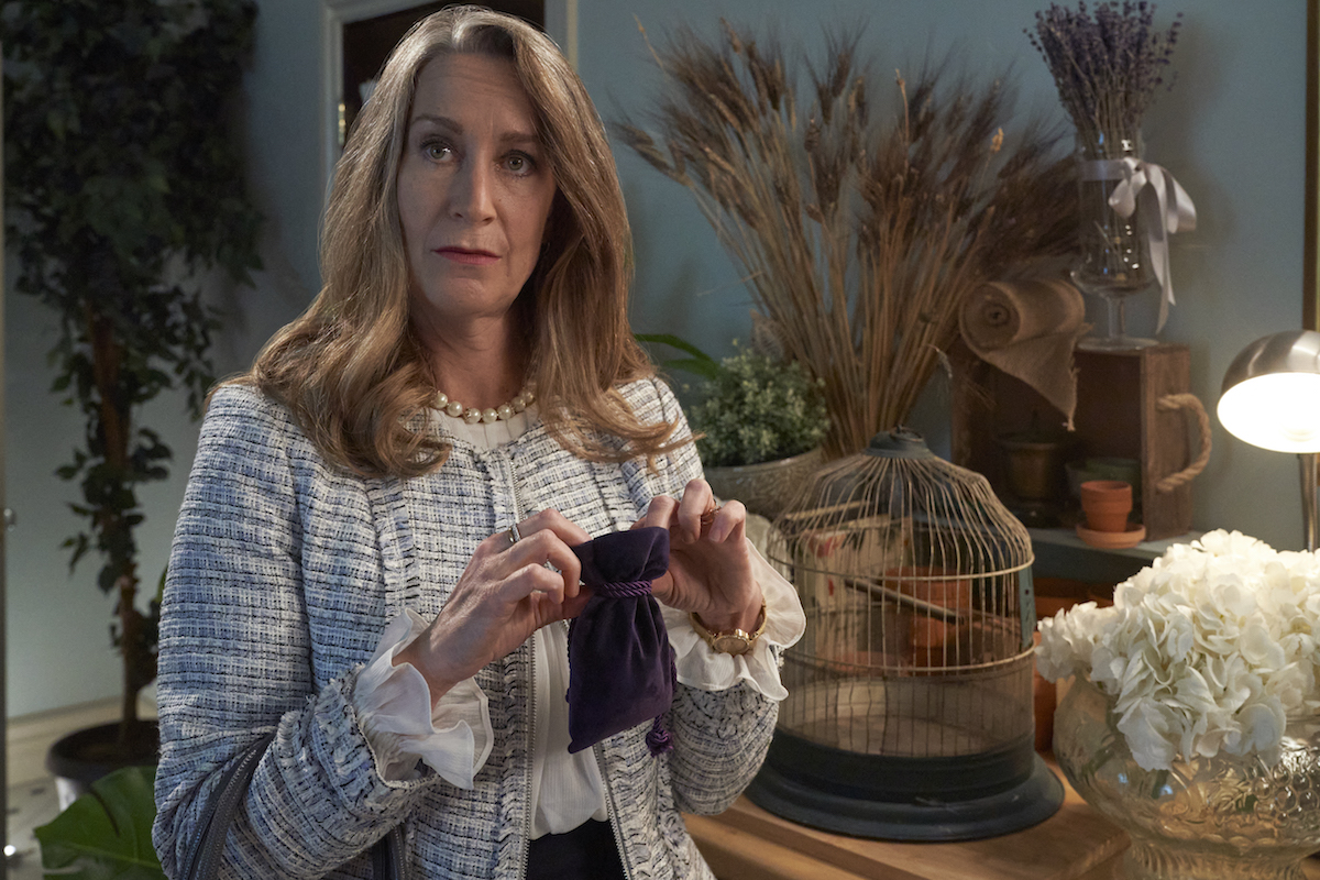 Blond woman holding purple velvet bag in Good Witch season 7 premiere