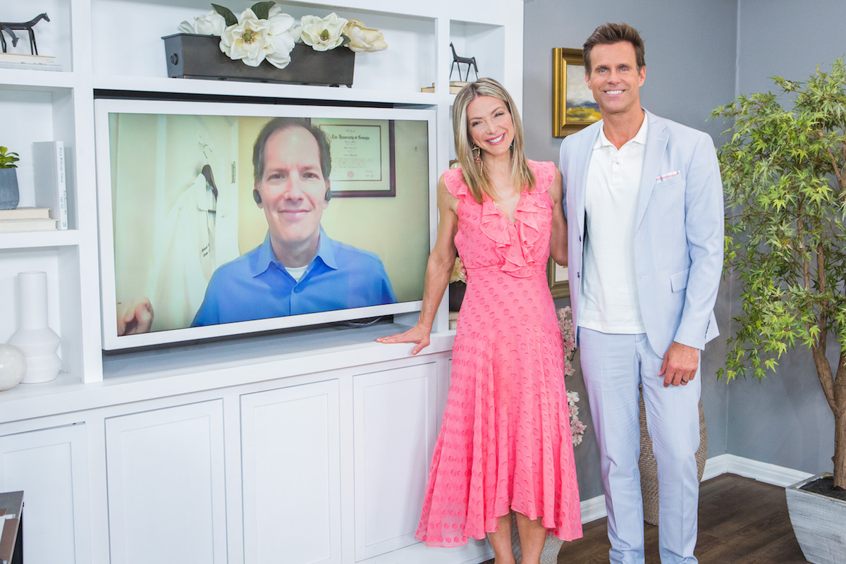 Home and Family hosts Debbie Matenopoulos and Cameron Mathison standing next to a TV screen
