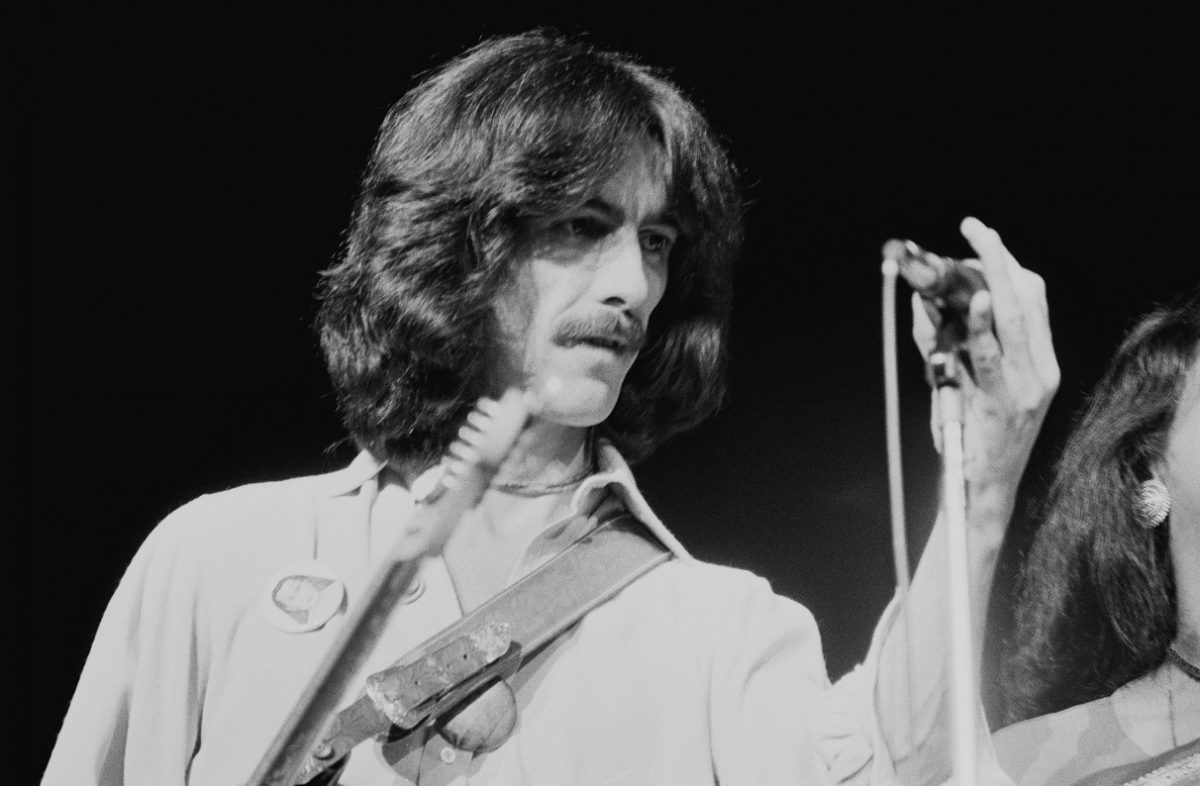 George Harrison adjusts a microphone on stage in 1974.