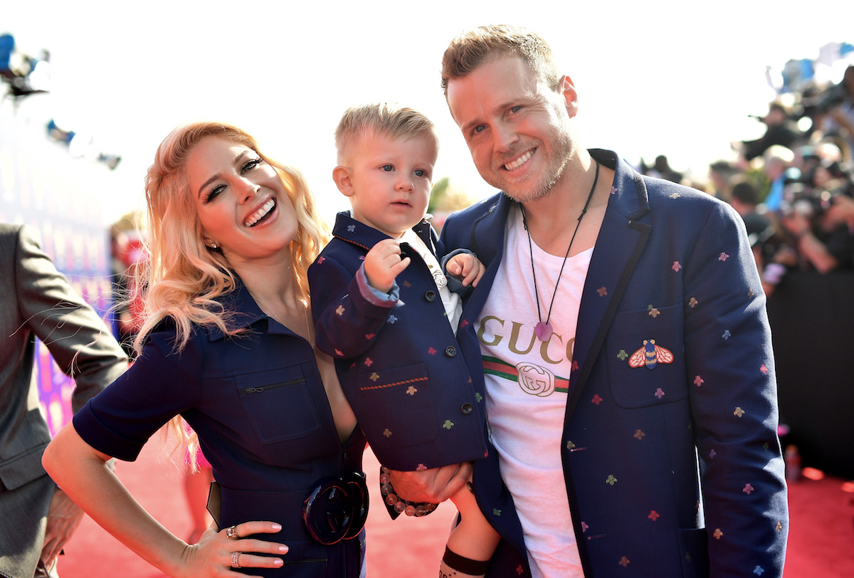 Spencer Pratt holding his son and standing next to Heidi Montag