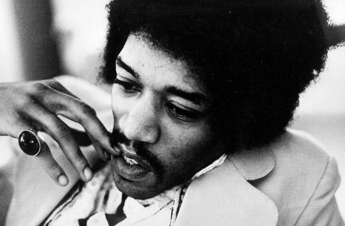 Jimi Hendrix holds his fingers to his face as he stares off-camera
