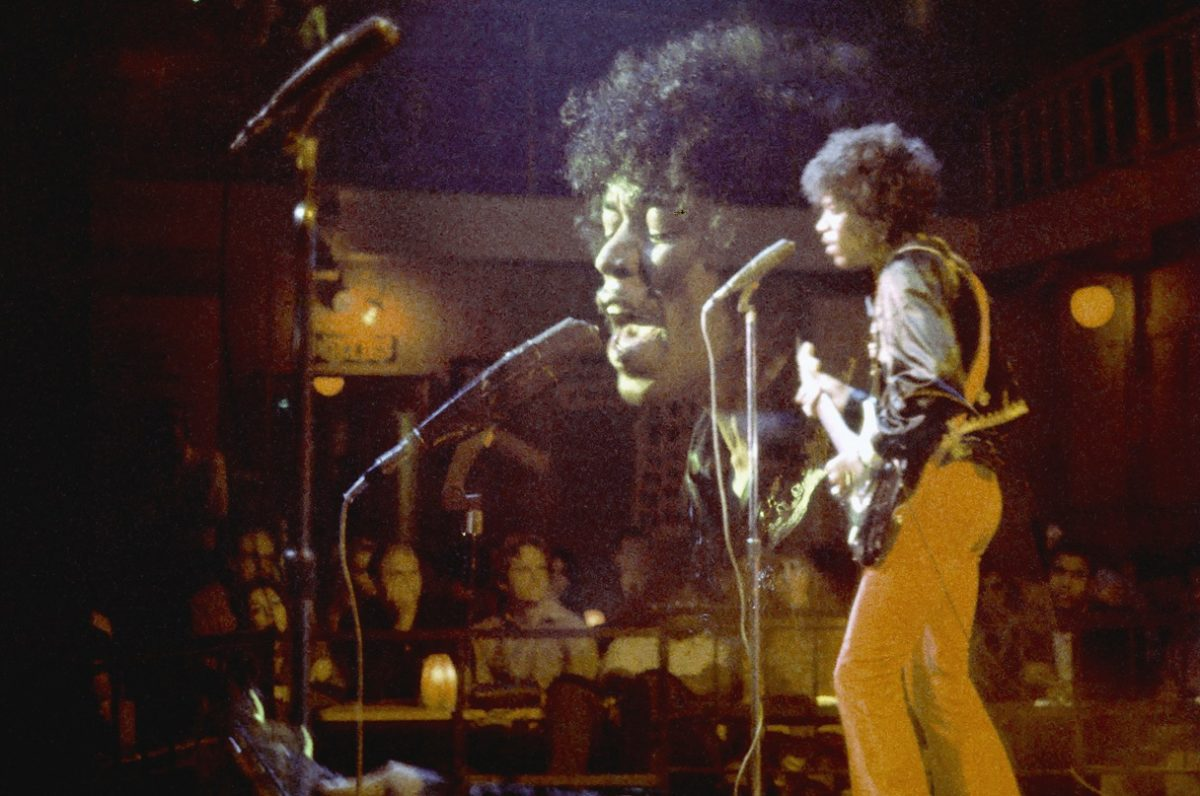 Jimi Hendrix performs on a stage in front of an audience
