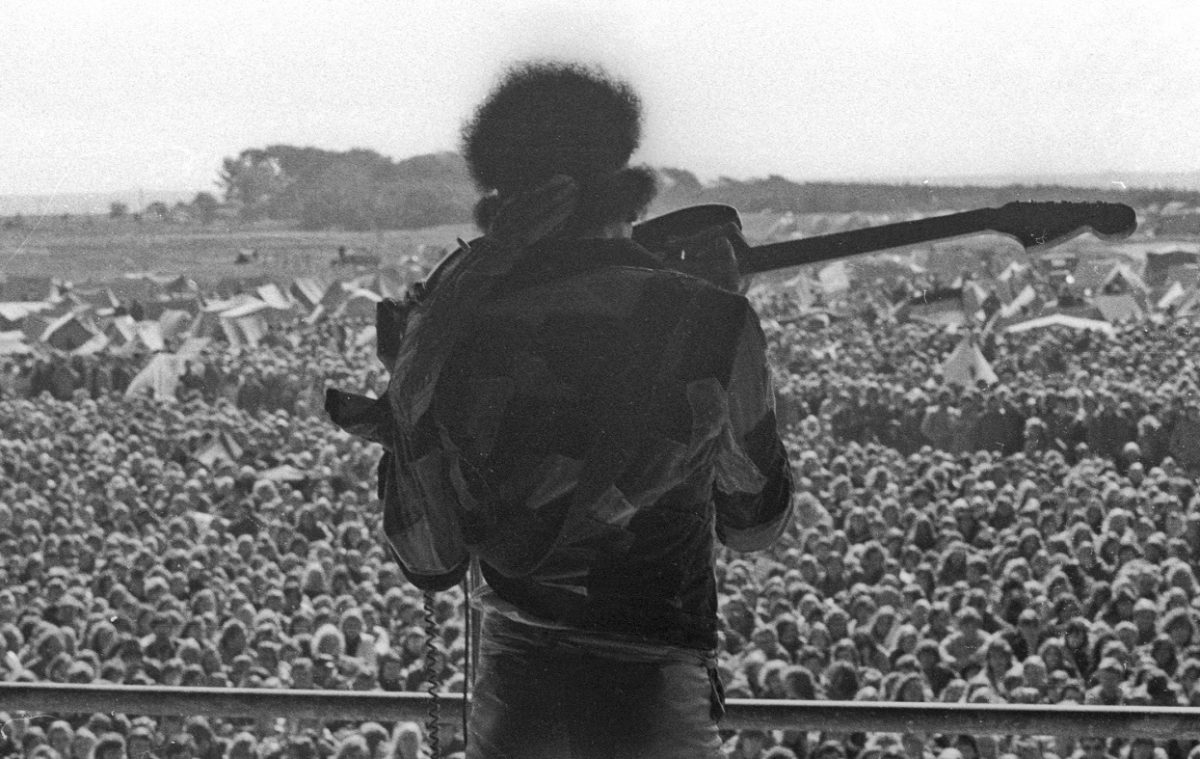 View from behind of Jimi Hendrix playing the guitar with his teeth, with a sea of fans in the background