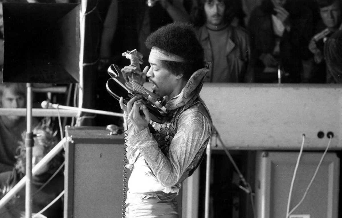 Side view of Jimi Hendrix playing the guitar with his teeth on stage in 1970