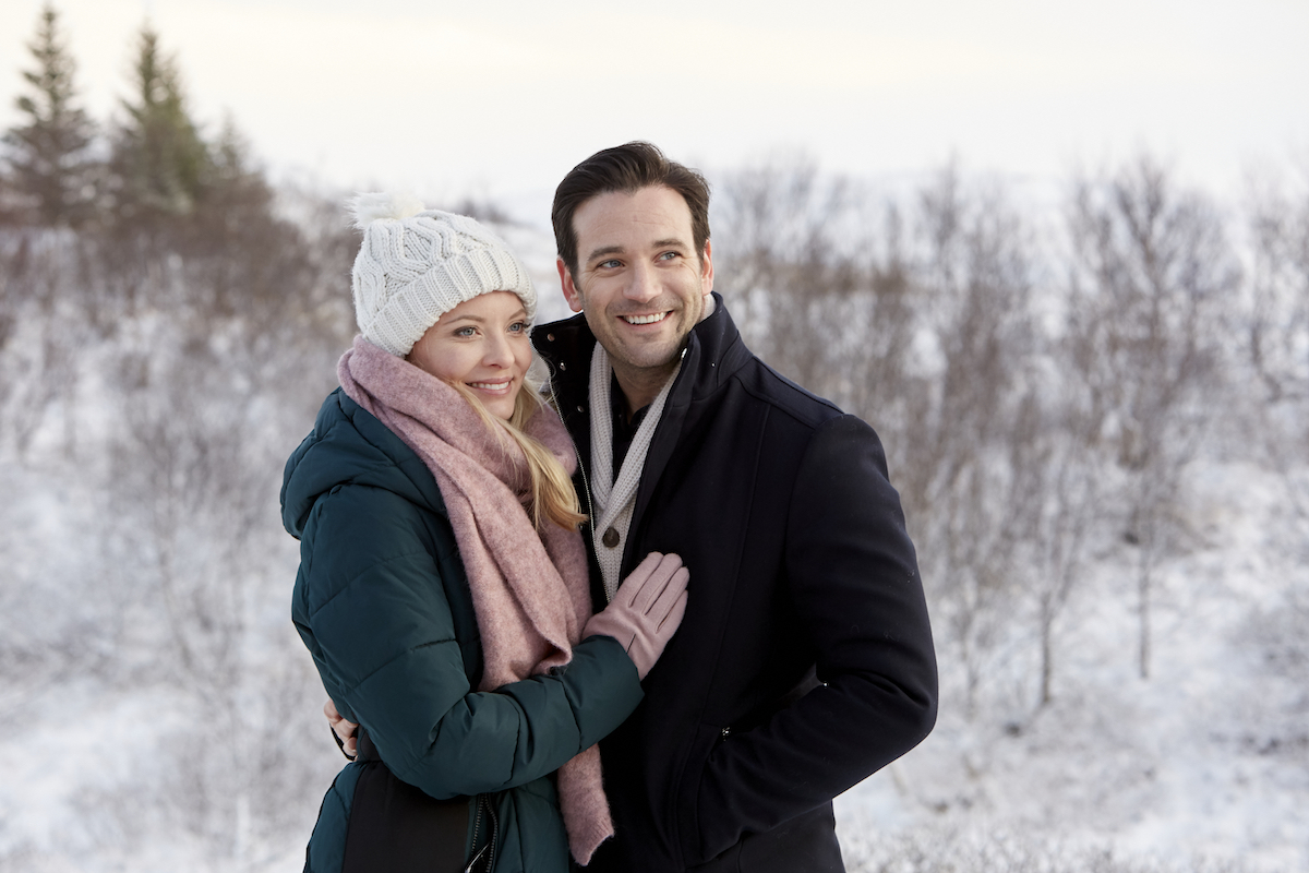 Woman in white hat and green coat with her arms around man in black coat in Hallmark Channel movie Love on Icelance