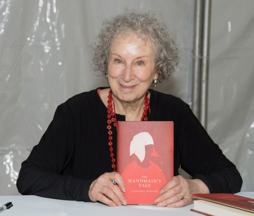 Margaret Atwood sitting and holding a copy of The Handmaids Tale
