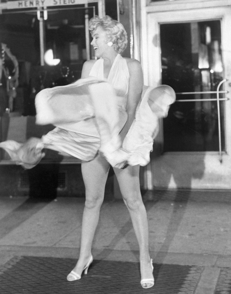 Actress Marilyn Monroe tries to hold down her dress as wind from a subway grate blows it upward
