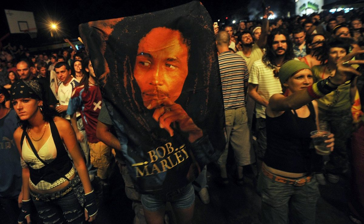Serbian villagers hold a Bob Marley blanket while attending the unveiling of a Marley statue.