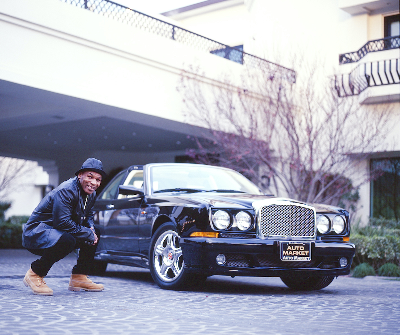Mike Tyson poses at his home in 2000 with his Jaguar and Bentley