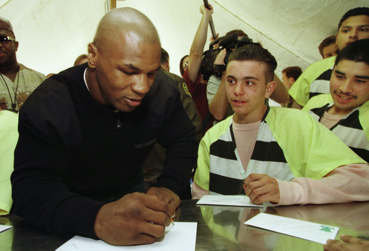 """Teenage inmate Philip Hagadorn, center, watches as former heavyweight boxing champion Mike Tyson signs autographs at the Maricopa County """"Pup Tent City"""" jail facility"""