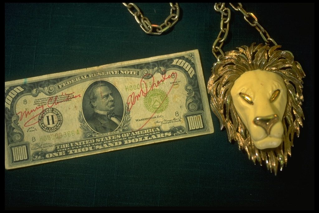 A thousand dollar bill owned by Elvis Presley next to a lion necklace