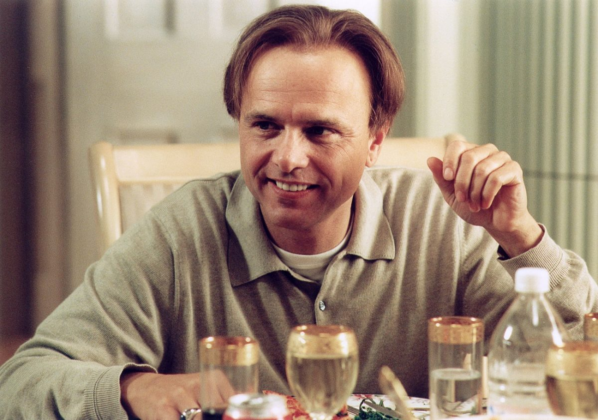 Joe Pantoliano smiles in character as Ralph Cifaretto seated at the dinner table
