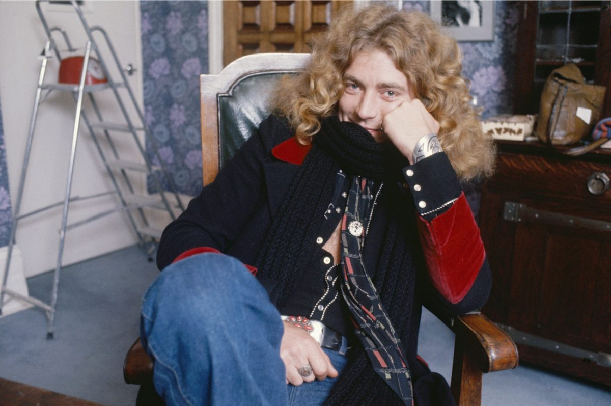 A seated Robert Plant smiles and looks at the camera in 1975.