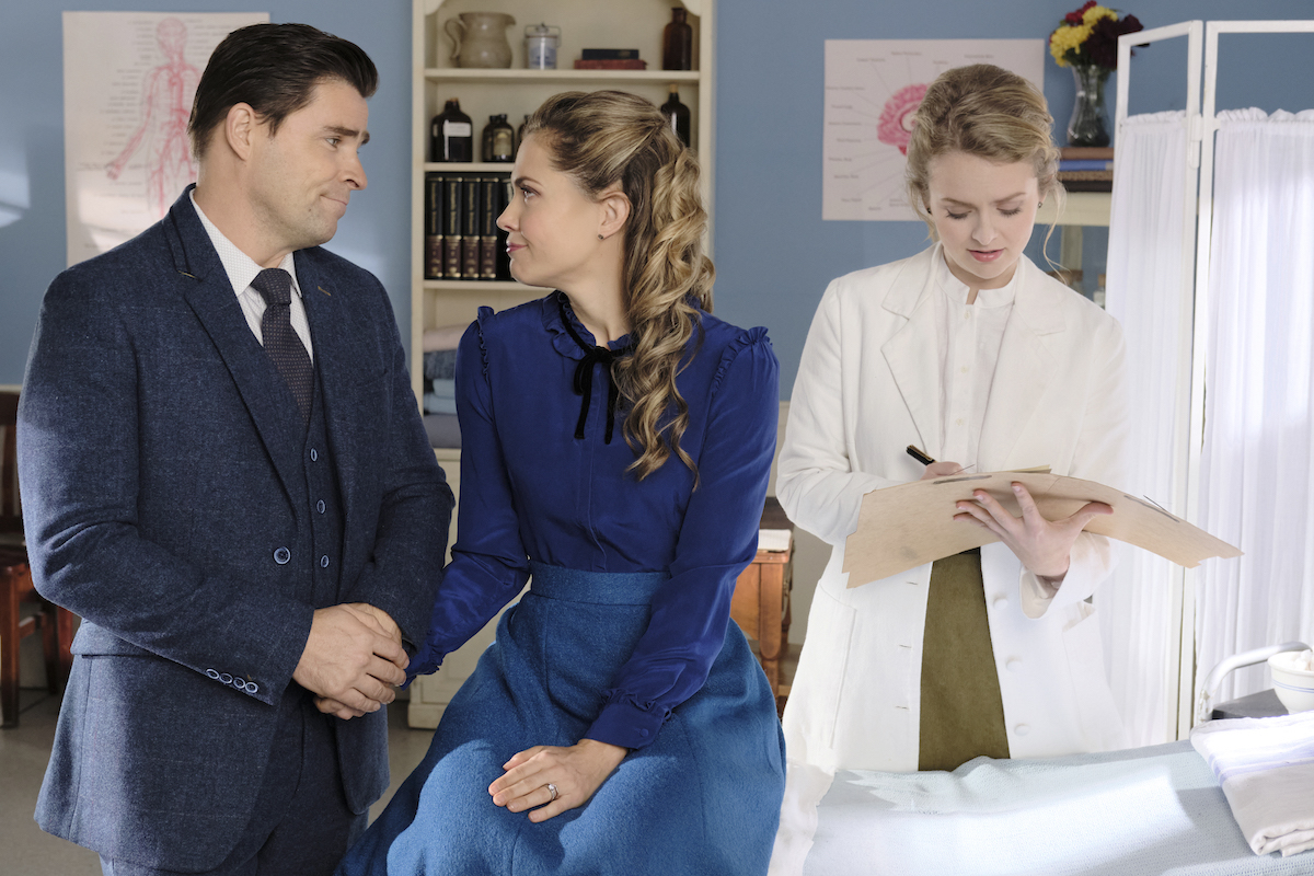 Rosemary and Lee holding hands while Faith makes notes in an episode of When Calls the Heart