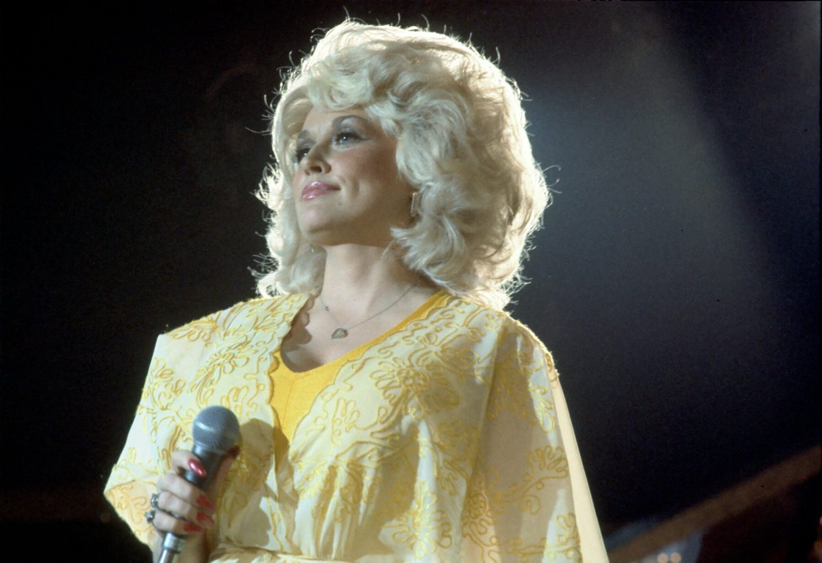 Dolly Parton performs onstage wearing a yellow dress in 1975 in Los Angeles, California.