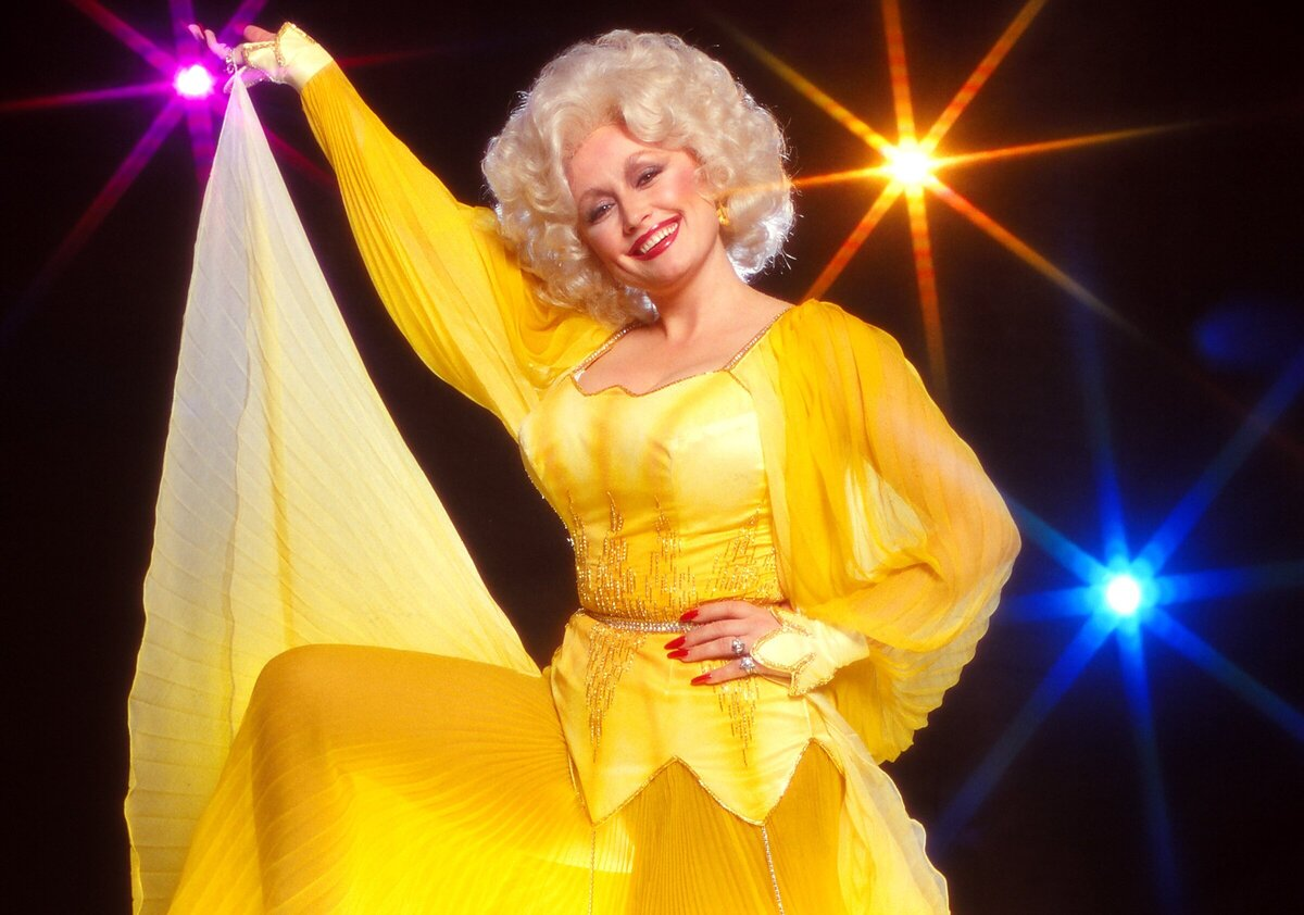 Dolly Parton poses for a portrait in a bright yellow dress with her signature big blonde hair.