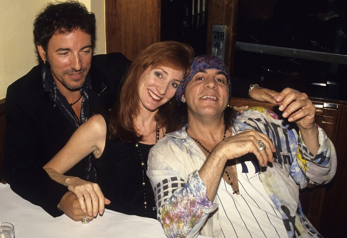 Bruce Springsteen, Patti Scialfa, and Steven Van Zandt embrace and smile for the camera in a restaurant booth.