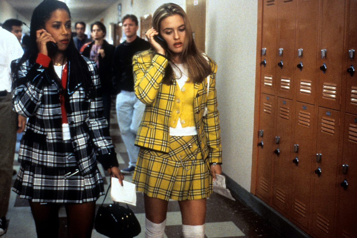 Stacey Dash and Alicia Silverstone walking down high school hallway while talking on their phones in Clueless