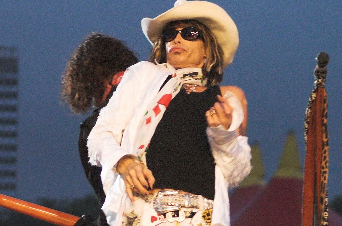 Steven Tyler plays air guitar on stage with Aerosmith