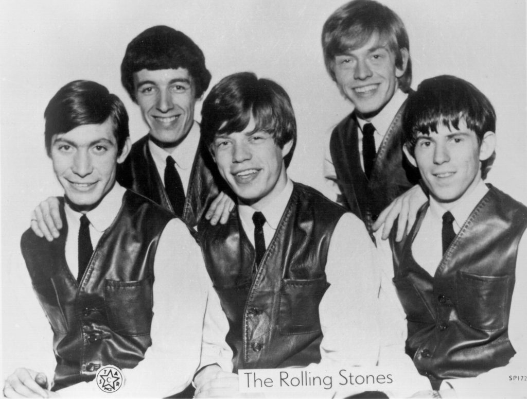 Mick Jagger sitting in the middle of The Rolling Stones