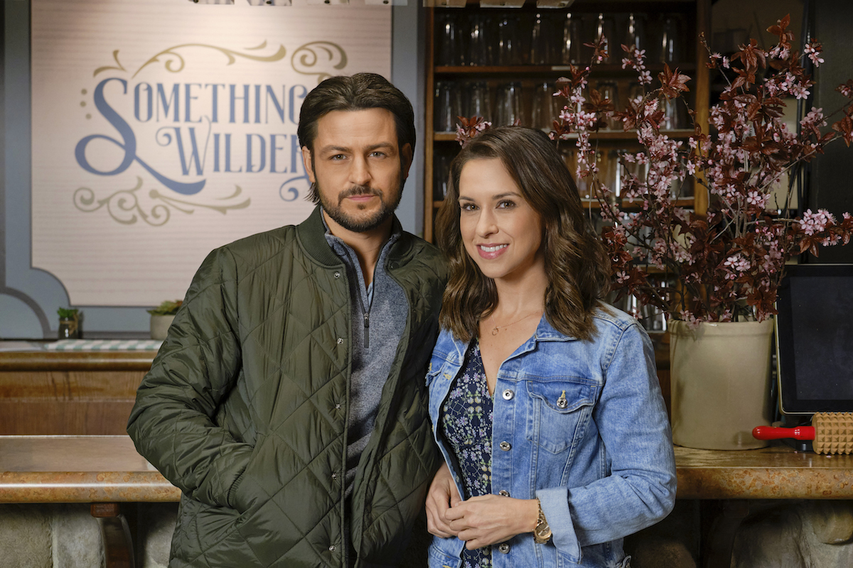 Tyler Hynes and Lacey Chabert standing next to each other in Sweet Carolina