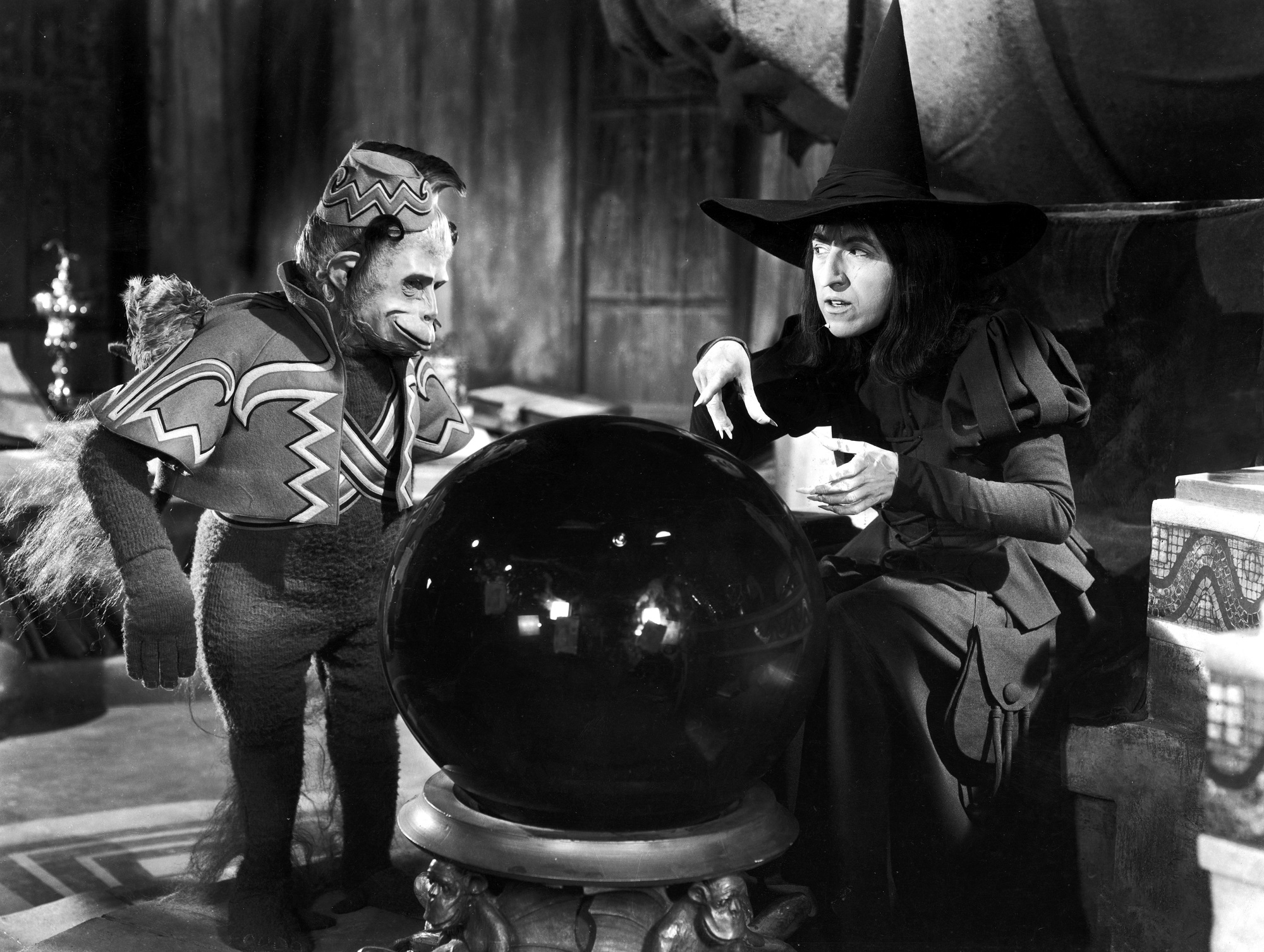 American actor Margaret Hamilton (1902 - 1985) and a winged monkey look into a crystal ball in a still from the film, The Wizard of Oz, directed by Victor Fleming, 1939