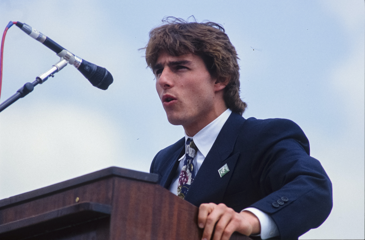 Tom Cruise wears a suit and speaks at a podium at the United States Capitol in 1990