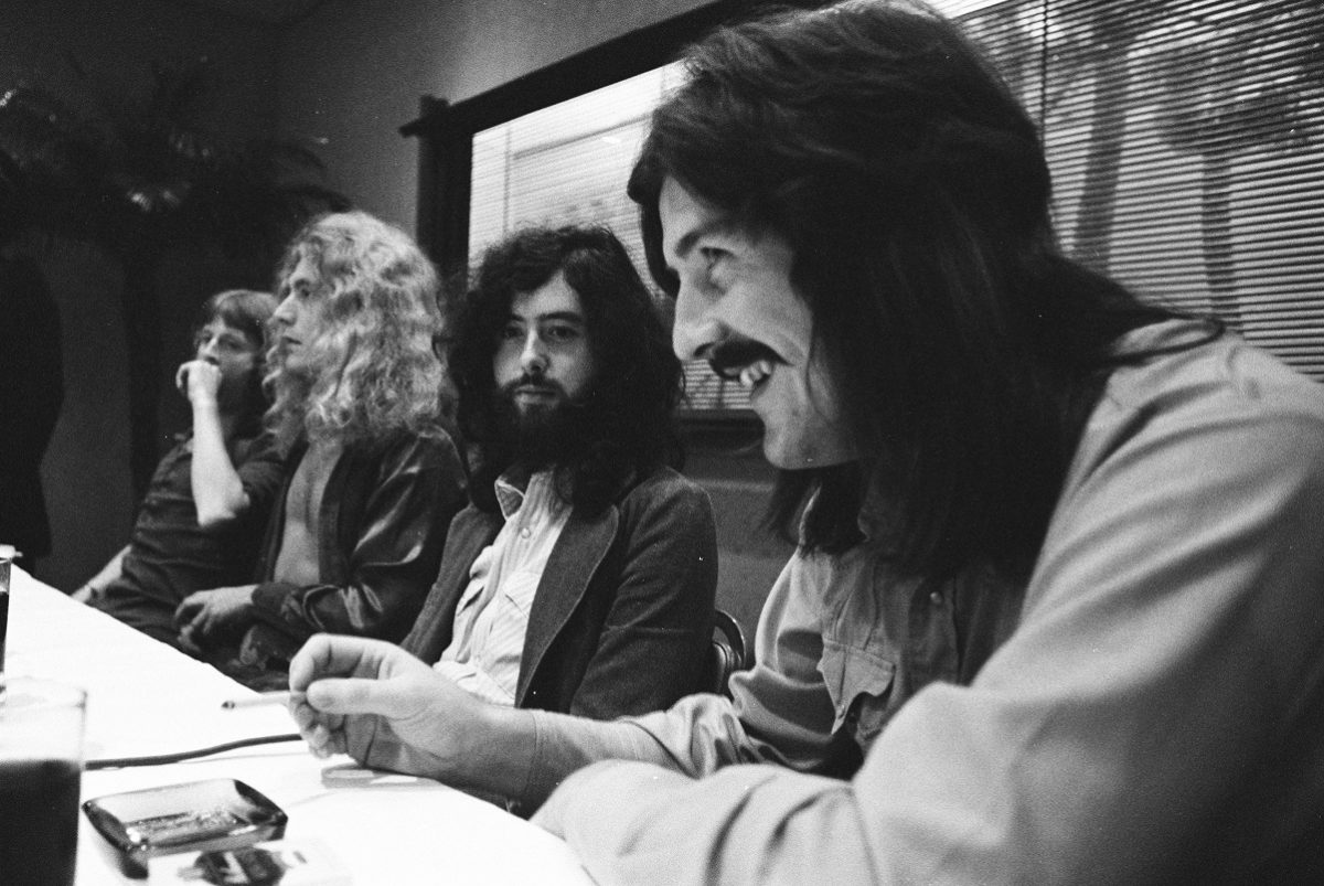 John Bonham laughs as Led Zeppelin band members look on during a press conference