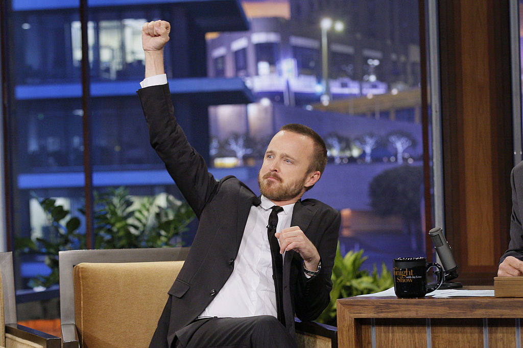 Actor Aaron Paul looks excited with an arm up in the air during an interview with Jay Leno.