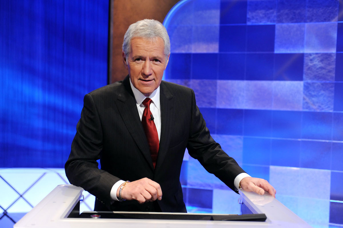The late Alex Trebek wears a suit and poses on the 'Jeopardy!' set