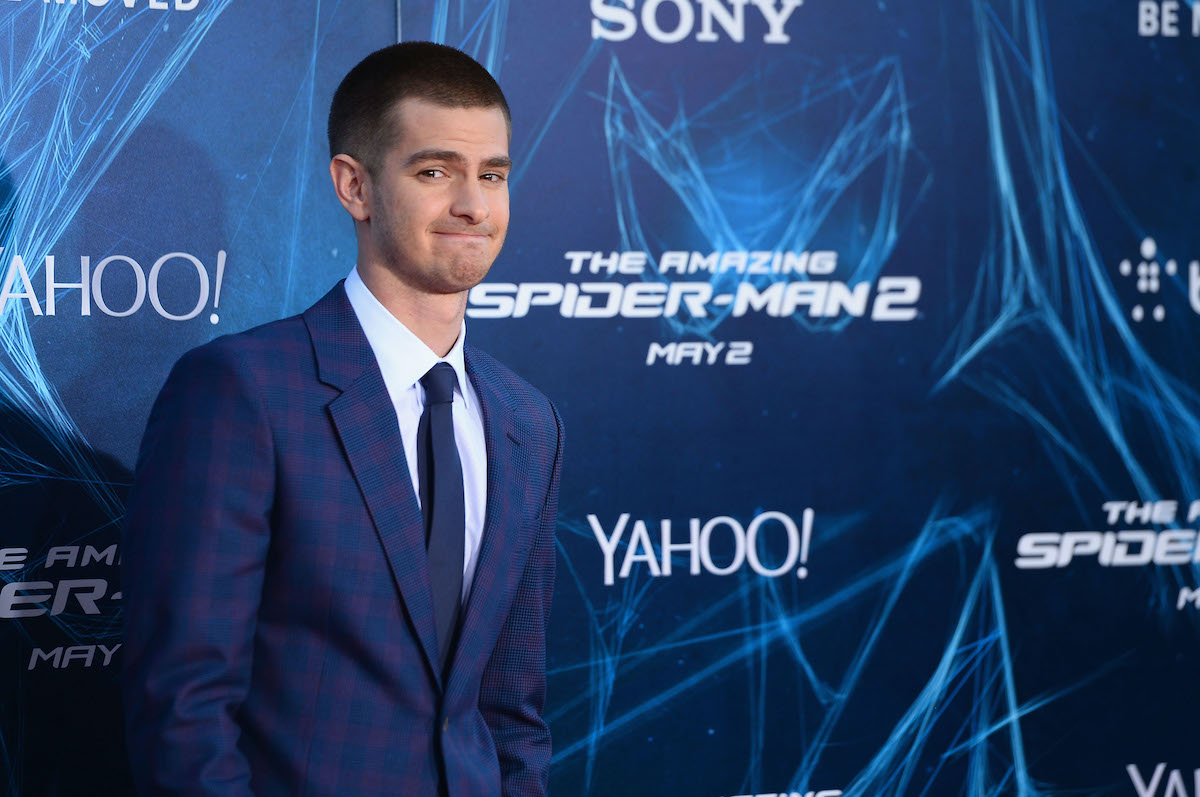 Andrew Garfield wears a blue suit and stands in front of a logo display of 'The Amazing Spider-Man 2'