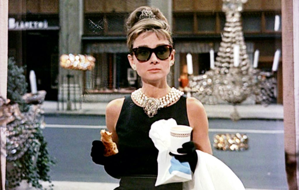 Audrey Hepburn in 'Breakfast at Tiffany's' standing in front of a window holding coffee