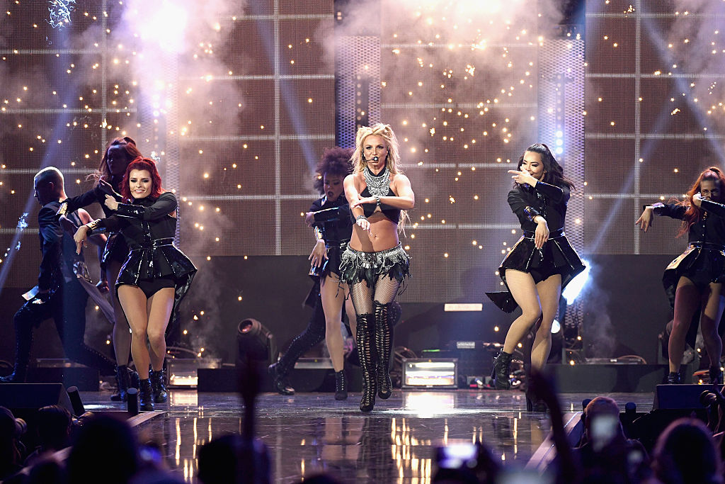 Britney Spears performs onstage with her dancers. She's wearing a mic set and black and silver costume.