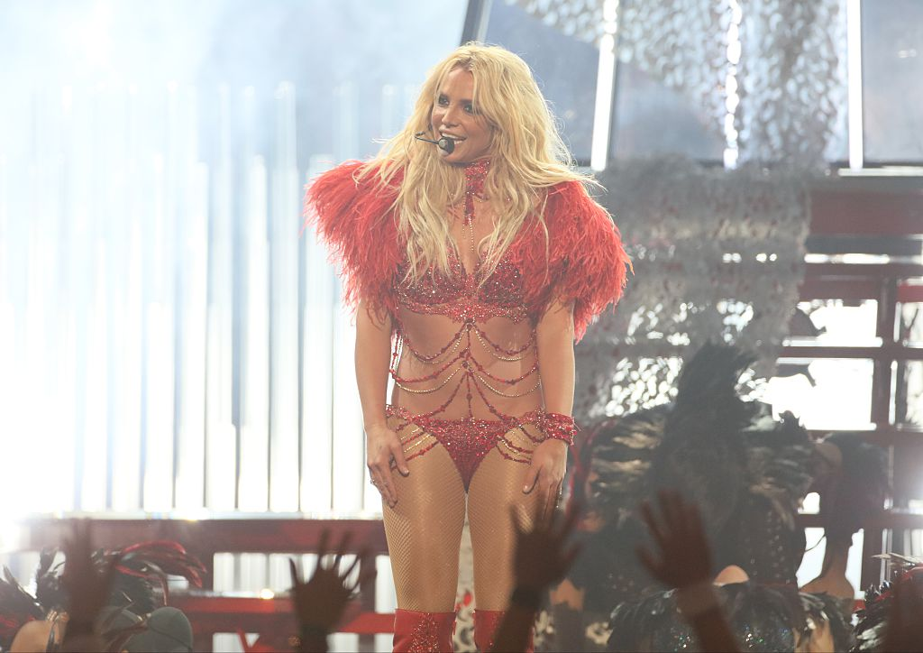 Britney Spears wears a red costume while performing on stage.