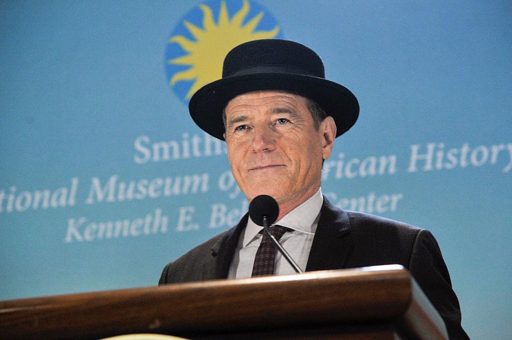 Bryan Cranston speaks at the Smithsonian while wearing his 'Heisenberg' hat.