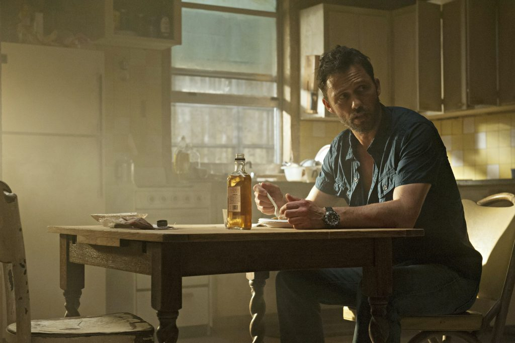 Jeffrey Donovan sitting at a table in a scene from 'Burn Notice'