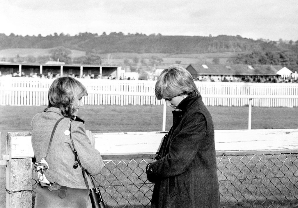 Camilla Parker Bowles and Lady Diana Spencer (later the Princess Diana) standing next to a fence at Ludlow racecourse