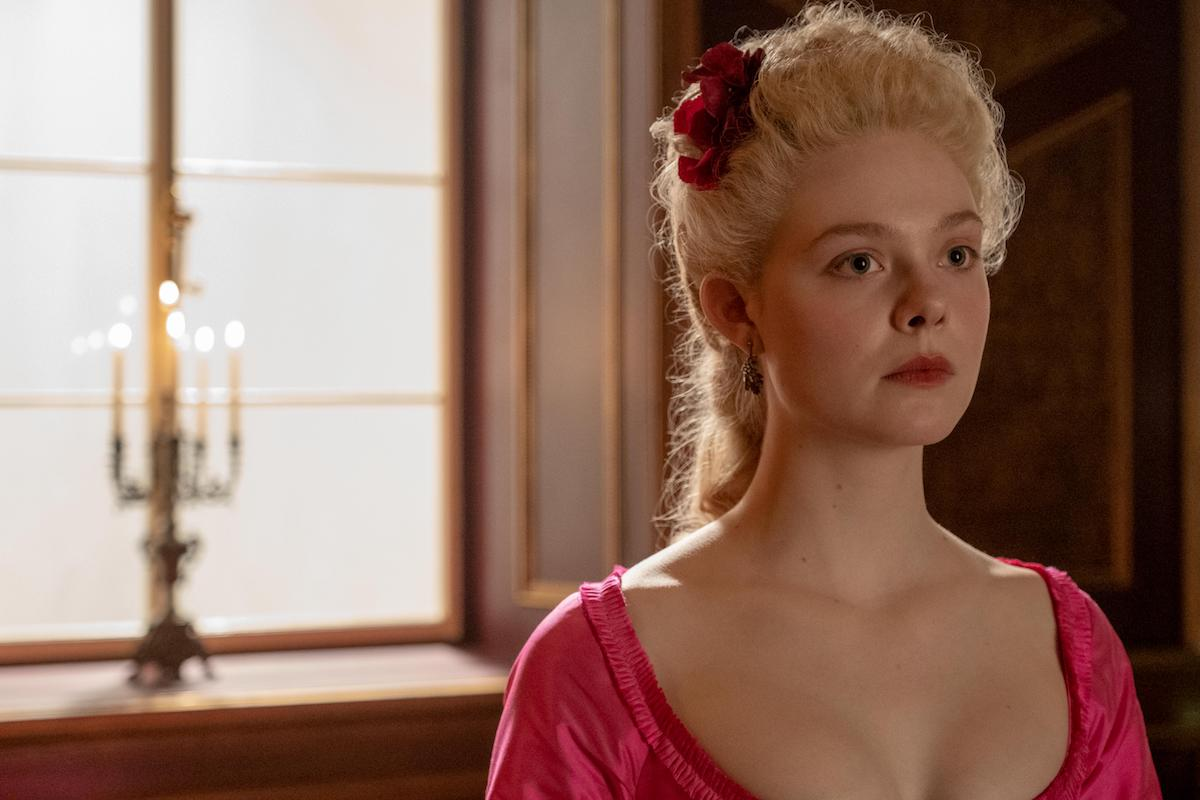 Elle Fanning as Catherine, wearing a pink dress and in front of a window, in 'The Great'