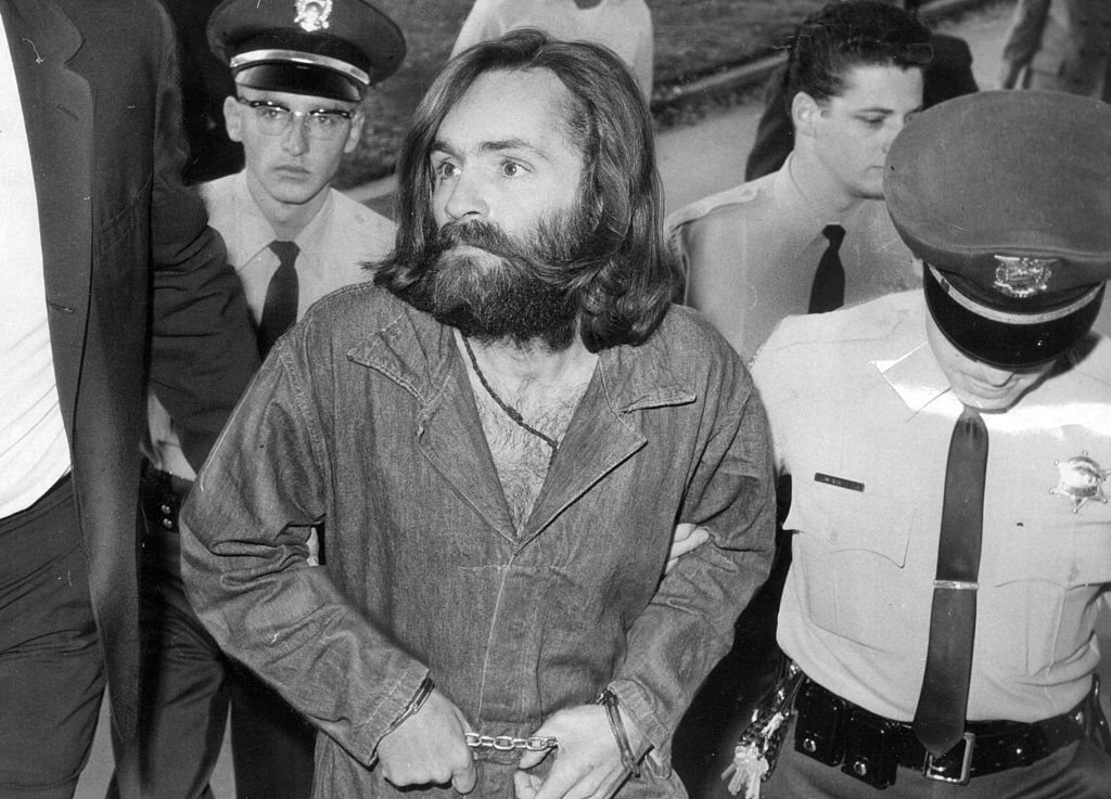 Charles Manson is escorted to court for preliminary hearing. He is dressed in a jumpsuit and shackles.